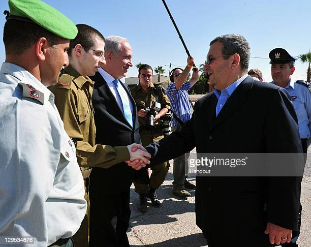 In this handout photo provided by the Israeli Defence Force freed Israeli soldier Gilad Shalit shakes hands with Defence Minister Ehud Barak next to...