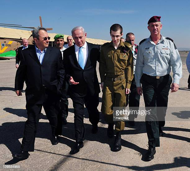 In this handout photo provided by the Israeli Defence Force freed Israeli soldier Gilad Shalit walks with Israeli Prime Minister Benjamin Netanyahu...