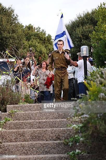 In this handout photo provided by the Israeli Defence Force freed Israeli soldier Gilad Shalit arrives at the steps of his family home on October 18...