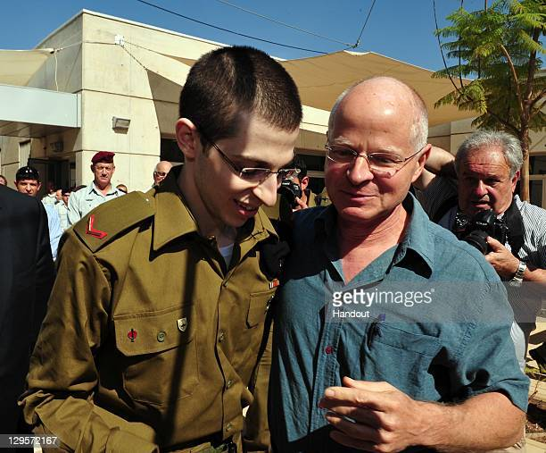 In this handout photo provided by the Israeli Defence Force freed Israeli soldier Gilad Shalit walks with his father Naom Shalit at Tel Nof Airbase...