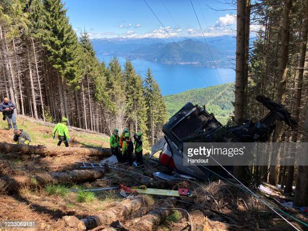 In this handout photo provided by the Italian National Alpine and Speleological Rescue Corps, emergency workers surround the wreckage of a cable car...