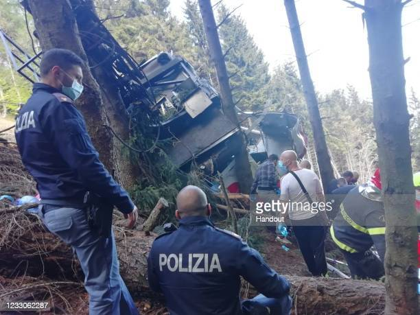 In this handout photo provided by the Italian state police, emergency workers surround the wreckage of a cable car that fell from the...