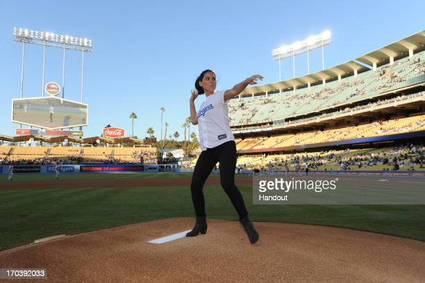In this handout photo provided by the Los Angeles Dodgers actress Olivia Munn visits Dodger Stadium to throw the first pitch before the Los Angeles...