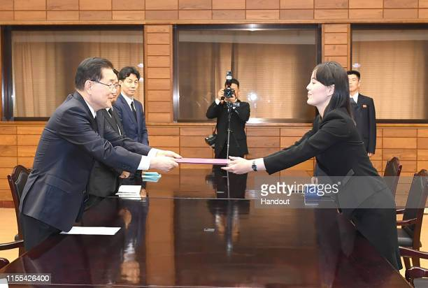 In this handout photo provided by the Ministry of Unification Kim YoJong sister of North Korean leader Kim Jong Un exchanges a document with Chung...