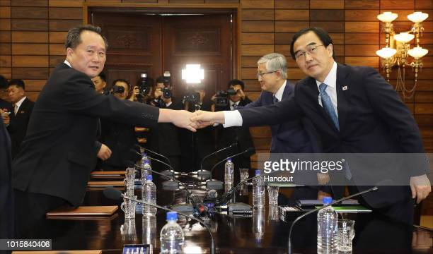 In this handout photo provided by the Ministry of Unification South Korean Unification Minister Cho MyoungGyon shakes hands with North Korean...