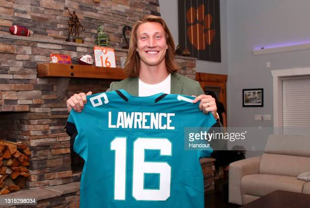 In this handout photo provided by the National Football League, quarterback Trevor Lawrence poses after being selected with the first overall pick by...