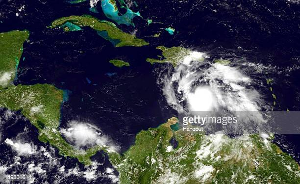 In this handout photo provided by the National Oceanic and Atmospheric Administration Tropical Storm Ernesto builds strength as it moves west August...