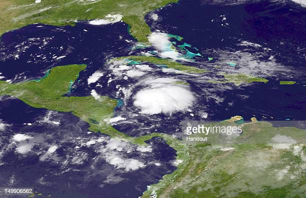 In this handout photo provided by the National Oceanic and Atmospheric Administration Tropical Storm Ernesto moves west along the coast of Honduras...