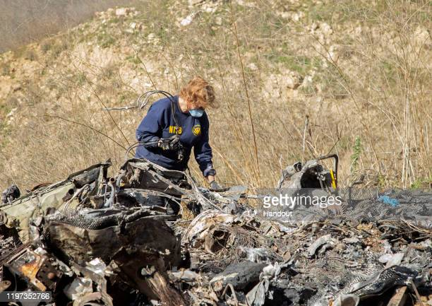 In this handout photo provided by the National Transportation Safety Board, an investigator works at the scene of the helicopter crash that killed...