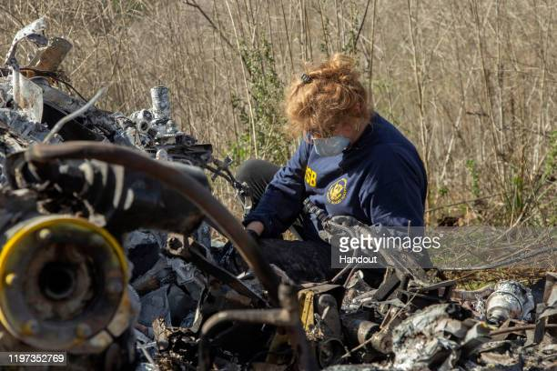 In this handout photo provided by the National Transportation Safety Board an investigator works at the scene of the helicopter crash that killed...