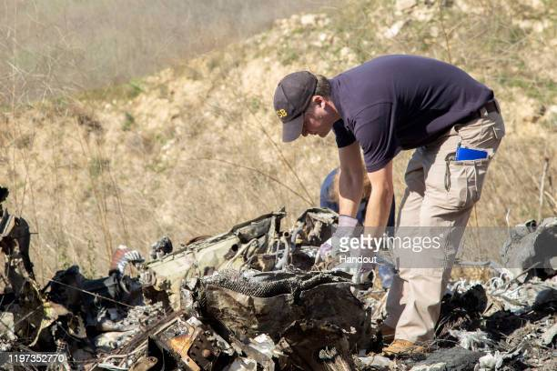 In this handout photo provided by the National Transportation Safety Board investigators work at the scene of the helicopter crash that killed former...