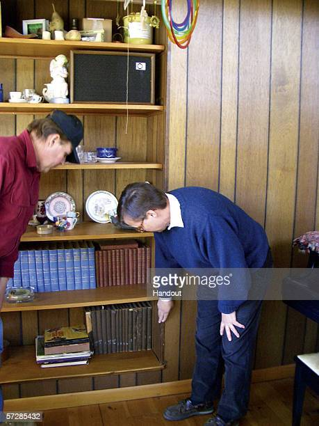 In this handout photo provided by the Norman Rockwell Museum Dave Trachte and Don Trachte Jr show the fake wall behind which they found the orginal...
