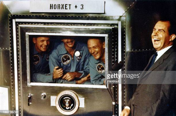 In this handout photo provided by the Richard Nixon Foundation Apollo XI astronauts Neil Armstrong Michael Collins and Buzz Aldrin laugh with...