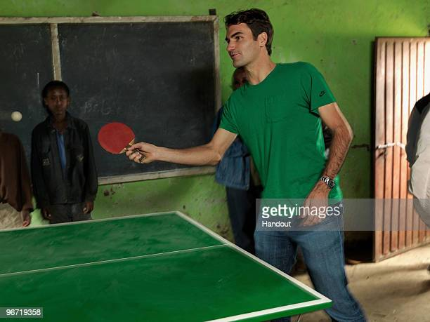 In this handout photo provided by the Roger Federer Foundation World tennis number one Roger Federer plays table tennis with local school children...