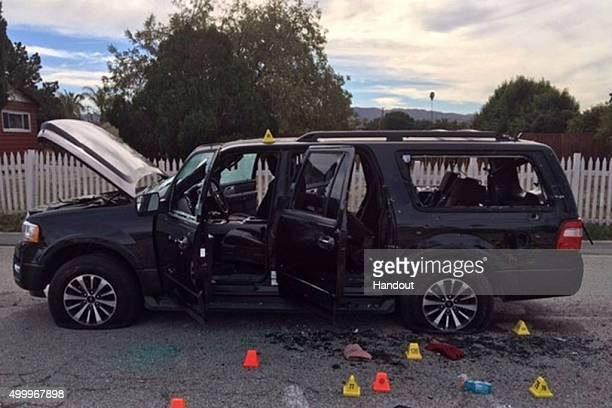 In this handout photo provided by the San Bernardino County Sherrif's Department evidence markers are scattered around an SUV near the site of a...