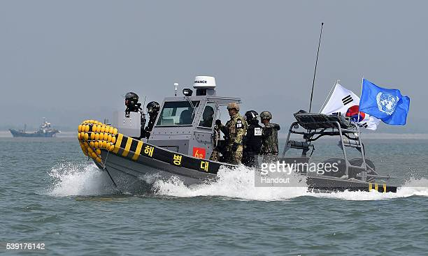 In this handout photo provided by the South Korean Defense Ministry South Korean marines and navy soldiers on a boat conduct a crackdown against...