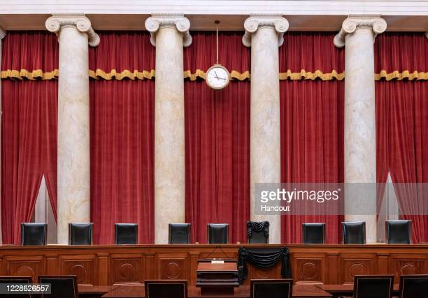In this handout photo provided by the Supreme Court of the United States, the bench and seat of Associate Justice Ruth Bader Ginsburg is draped in...
