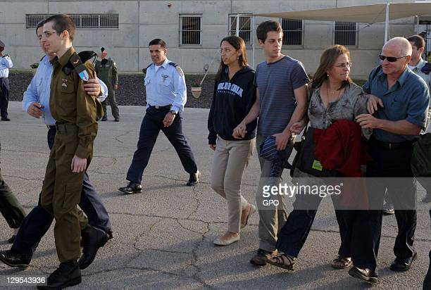 In this handout photo provided by the the Israeli Government Press Office freed Israeli soldier Gilad Shalit is followed by his family after meeting...