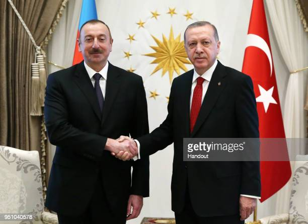 In this handout photo provided by The Turkish President Press office Turkish President Recep Tayyip Erdogan shake hands with Ilham Aliyev President...