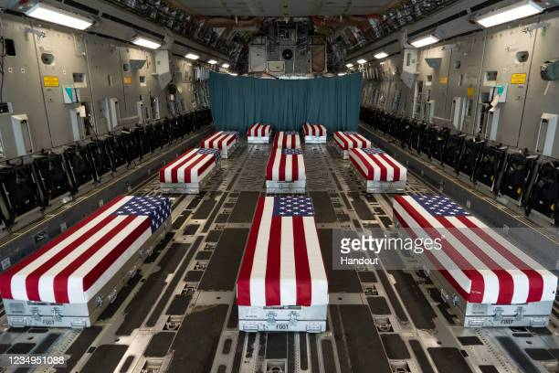 In this handout photo provided by the U.S. Air Force, flag-draped transfer cases line the inside of a C-17 Globemaster II Aug. 29 prior to a...