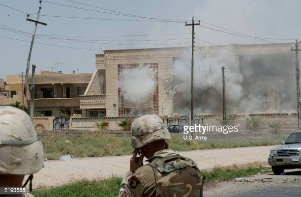 In this handout photo provided by the U.S. Army, dust and smoke billow from a building hit by a TOW missile launched by soldiers of the Army?s 101st...
