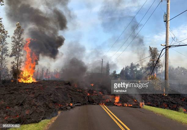 In this handout photo provided by the US Geological Survey lava from a fissure slowly advances to the northeast on Hookapu Street after the eruption...