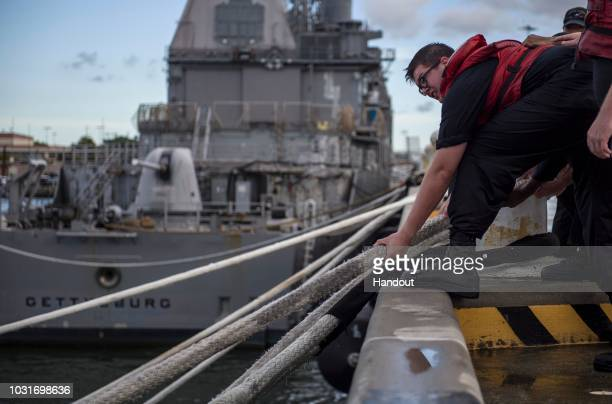 In this handout photo provided by the US Navy A sailor heaves line during a heavy weather mooring evolution in preparation for Hurricane Florence on...