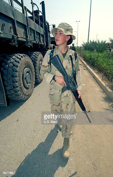 In this handout photo provided by the US Navy a US soldier assigned to Expeditionary Strike Group One prepares to distribute water to Iraqis October...