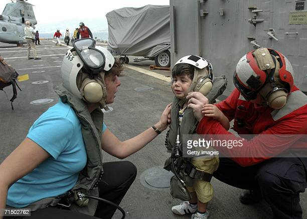 In this handout photo provided by the US Navy a woman comforts a small child after arriving aboard the amphibious transport dock USS Trenton by...