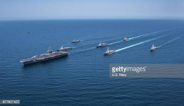In this handout photo provided by the US Navy F/A18 Hornets and Super Hornets from Carrier Air Wing Two fly over the Republic of Korea destroyers...