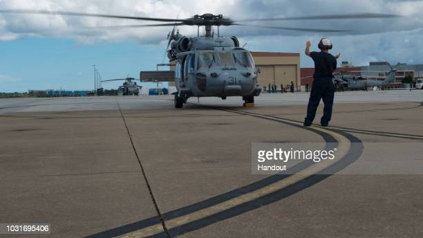 In this handout photo provided by the U.S. Navy, in anticipation of the arrival of Hurricane Florence, a MH-60S Sea Hawk helicopter attached to...