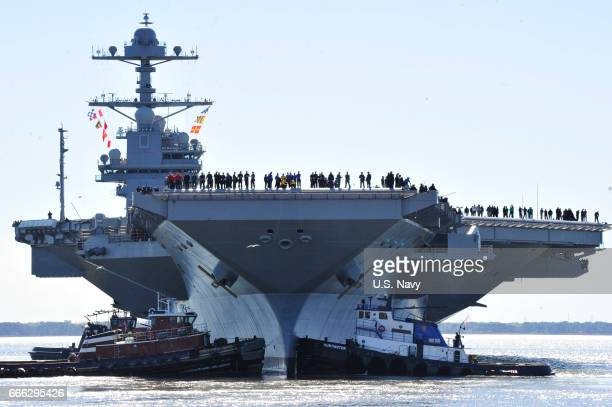 In this handout photo provided by the US Navy sailors aboard the aircraft carrier PreCommissioning Unit Gerald R Ford man the rails as the ship...