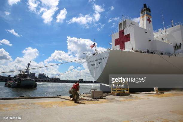 In this handout photo provided by the US Navy sailors cast off mooring lines for the Military Sealift Command hospital ship USNS Comfort at Naval...