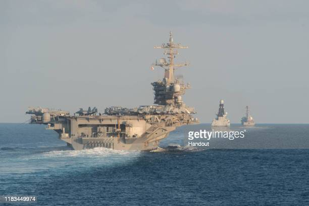 In this handout photo provided by the US Navy The aircraft carrier USS Abraham Lincoln left the Royal Navy air defense destroyer HMS Defender and the...