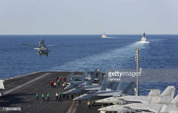 In this handout photo provided by the US Navy The aircraft carrier USS Abraham Lincoln transits the Strait of Hormuz as an MH60S Sea Hawk helicopter...