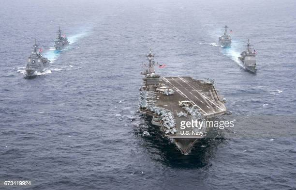 In this handout photo provided by the US Navy the aircraft carrier USS Carl Vinson leads the US Navy guidedmissile cruiser USS Lake Champlain right...