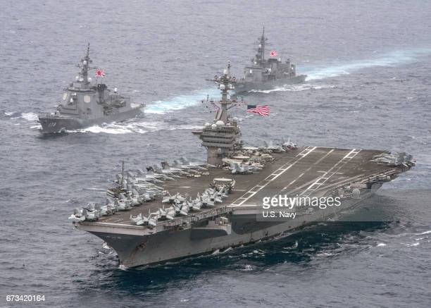 In this handout photo provided by the U.S. Navy, the aircraft carrier USS Carl Vinson , foreground, transits the Philippine Sea with the Japan...
