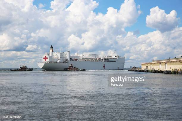 In this handout photo provided by the US Navy The Military Sealift Command hospital ship USNS Comfort evacuates from Naval Station Norfolk in...