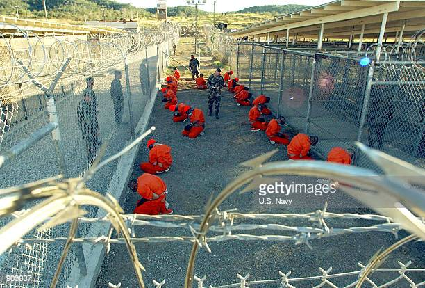 In this handout photo provided by the U.S. Navy, U.S. Military Police guard Taliban and al Qaeda detainees in orange jumpsuits January 11, 2002 in a...