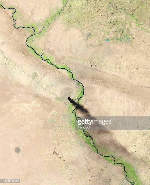 In this handout photo provided by the USGS A satellite view shows smoke billowing from the Baiji North refinery complex on June 18 2014 in Baiji...