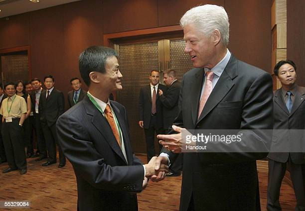 In this handout photo provided by the WCPV Jack Ma the CEO of Alibabacom shakes hands with former US president Bill Clinton during the Fifth China...