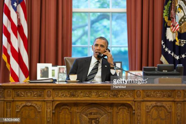 In this handout photo provided by the White House, President Barack Obama speaks with President Hassan Rouhani of Iran during a phone call in the...