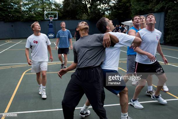 In this handout photo provided by the White House President Barack Obama plays basketball with cabinet secretaries and members of Congress on the...