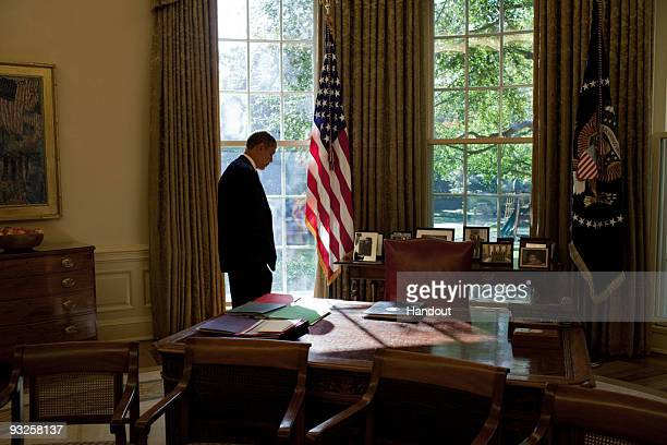 In this handout photo provided by the White House President Barack Obama walks to his desk in between meetings in the Oval Office of the White House...