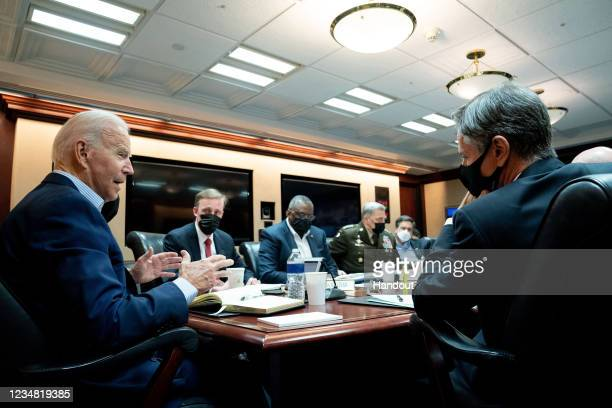 In this handout photo provided by the White House, President Joe Biden meets with his national security team for an operational update on the...