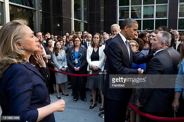 In this handout photo provided by The White House US President Barack Obama shakes hands with employees in a courtyard at the State Department as...