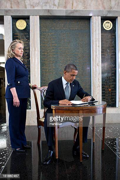In this handout photo provided by The White House US President Barack Obama signs a condolence book in memory of Ambassador Chris Stevens as...