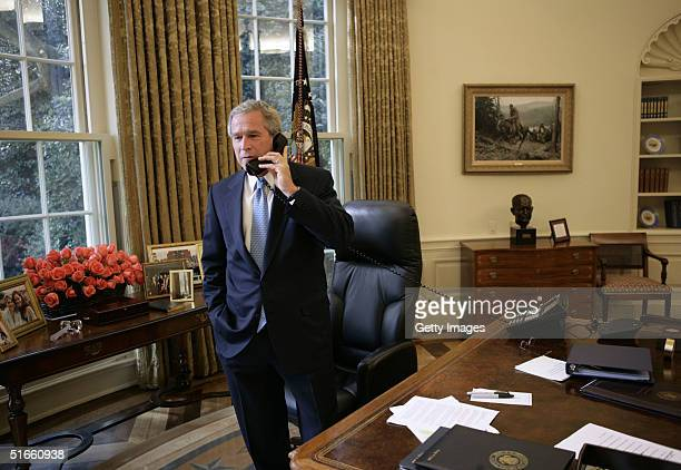 In this handout photo provided by the White House US President George W Bush takes a phone call in the Oval Office of the White House from Democratic...
