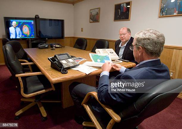 In this handout photo provided by the White House US President George W Bush takes a map from Deputy Chief of Staff Joe Hagin during a video...
