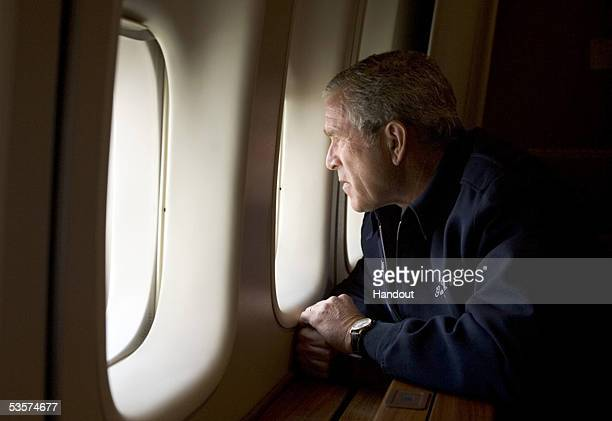 In this handout photo provided by the White House US President George W Bush looks out over devastation from Hurricane Katrina as he heads back to...